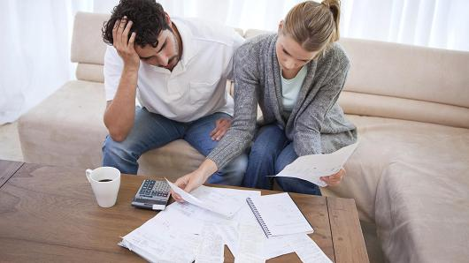 Stressed couple looking at bills.