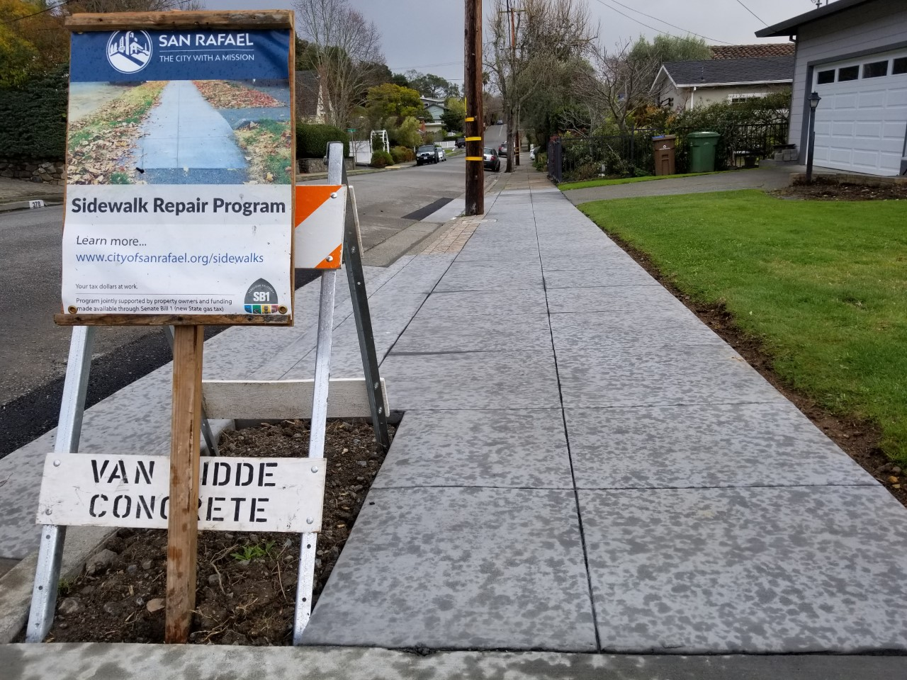 Sidewalk repair program sign along newly repaired sidewalks