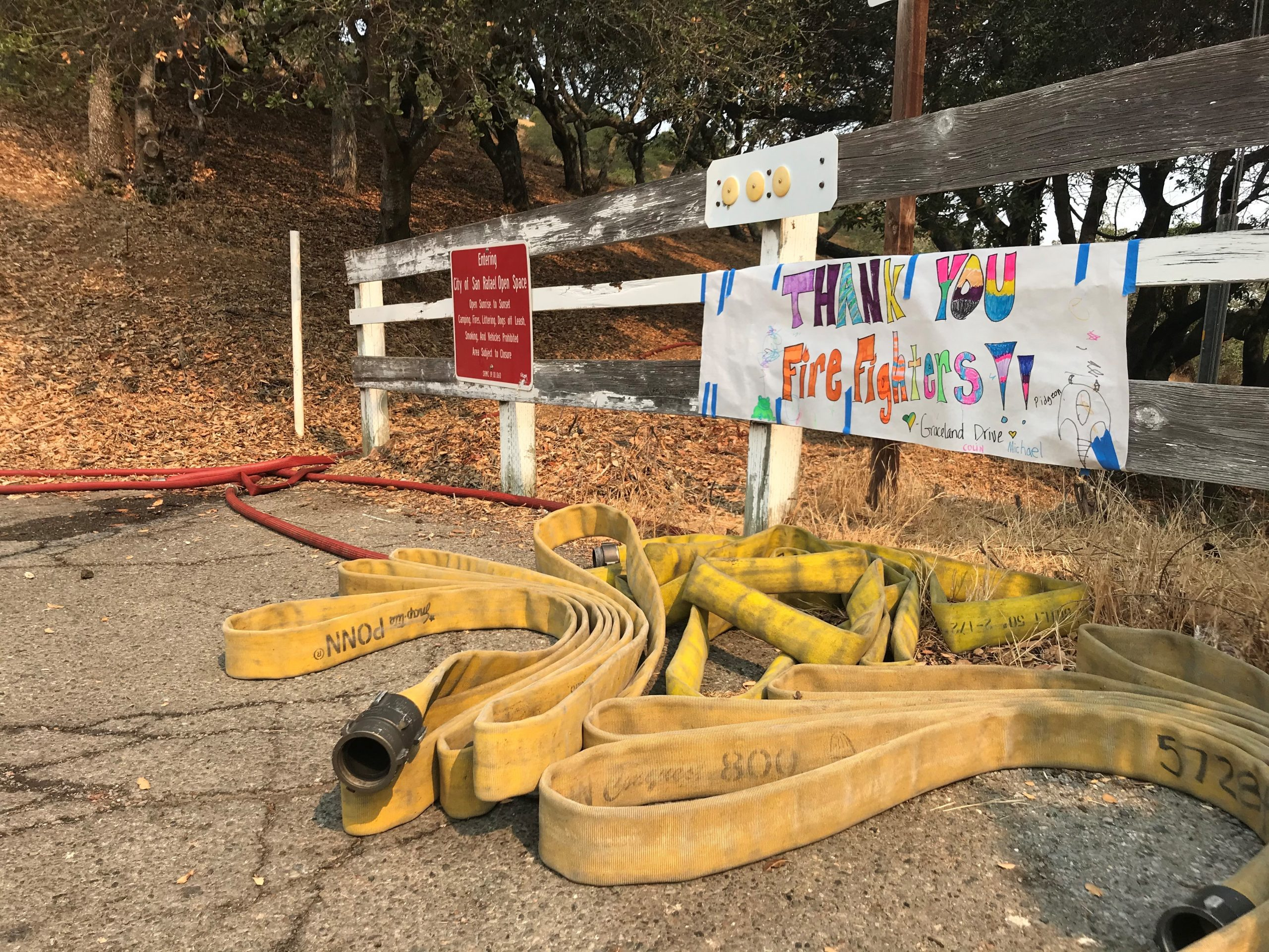 fire hose lays on the group in front of a hand written sign on a white fence that says Thank You Firefighters