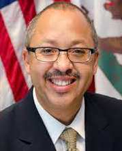 Headshot of Jones in a suit with  US and CA flags in background