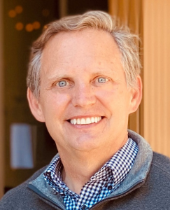Headshot of Klein smiling in checkered button-up and fleece pullover