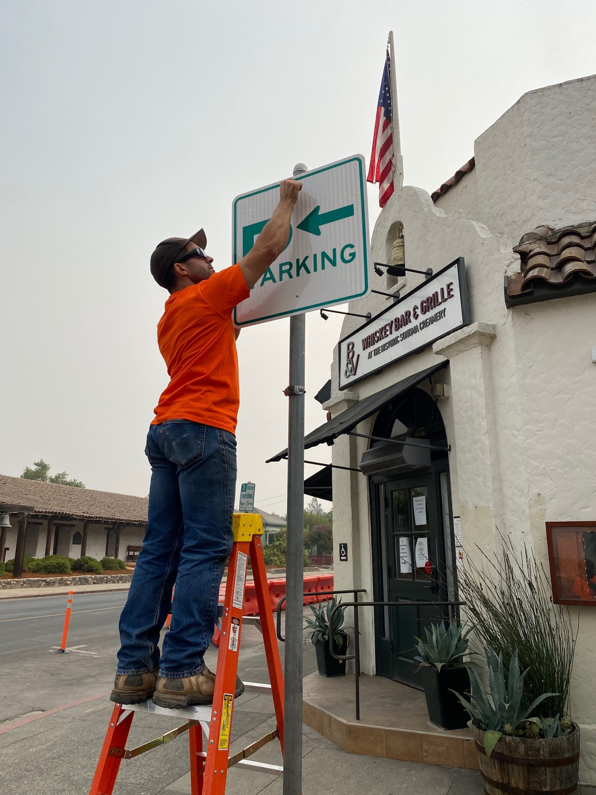 City Public Works Staff Installing a New Directional Parking Sign on the Plaza.