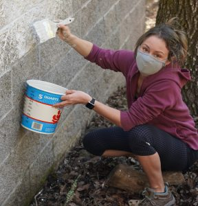 Volunteer Stephanie White helps paint over graffiti in Mountain Cemetery