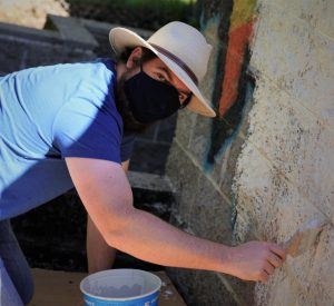Mayor Logan Harvey helps paint over graffiti at Mountain Cemetery