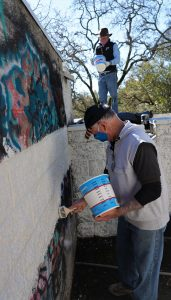 Wayne Schake and Gary Edwards painting over graffiti at Mountain Cemetery