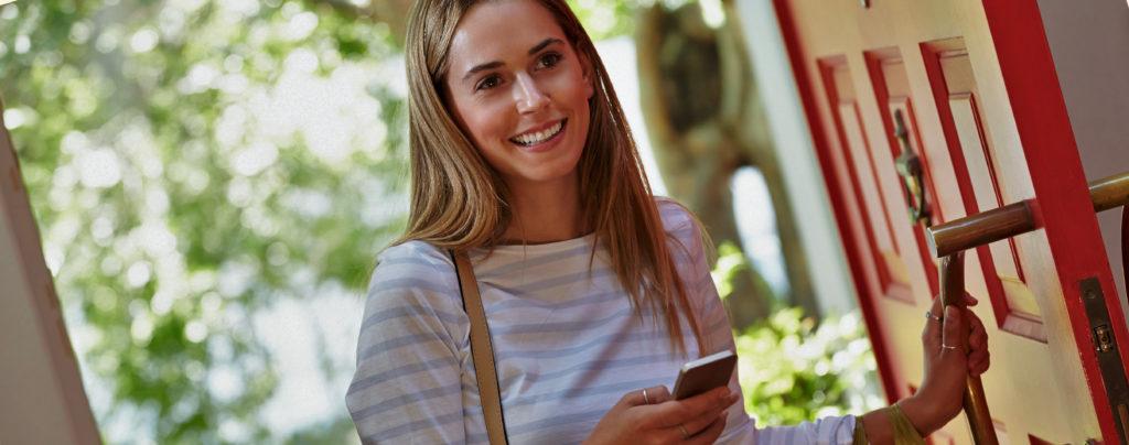 Glad kvinna öppnar en dörr och håller i en smartphone