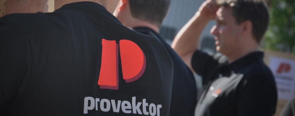 Provektoranställda med profilkläder. Fokus på närmsta personens rygg med en stor Provektorlogga.