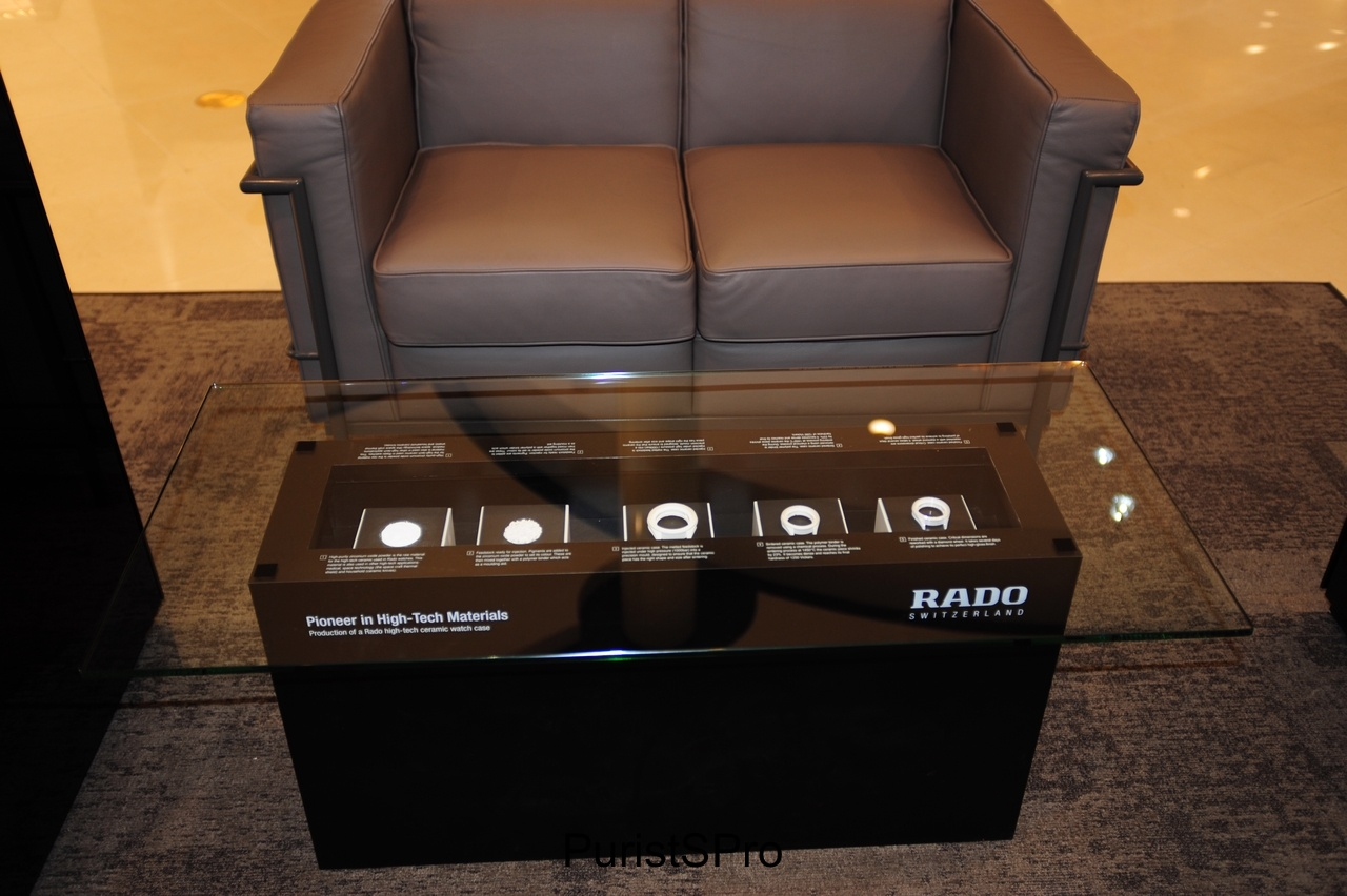 A lounge seating area with an innovative RADO coffee table display. The display shows the ceramic manufacturing process.