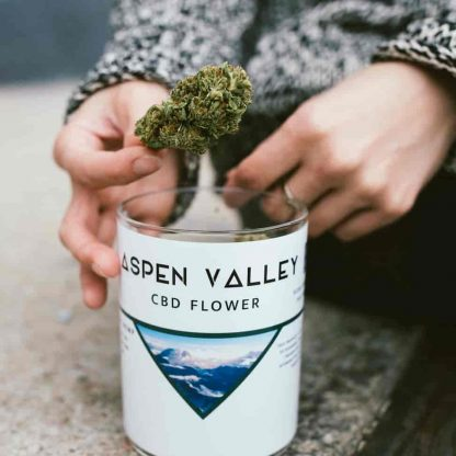 A female hand grabbing a delicious-looking CBD Hemp nugget out of a jar of CBD flower