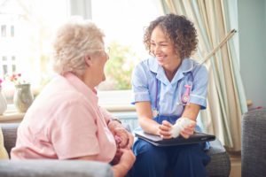 a senior woman speaking to a nurse at her senior living community