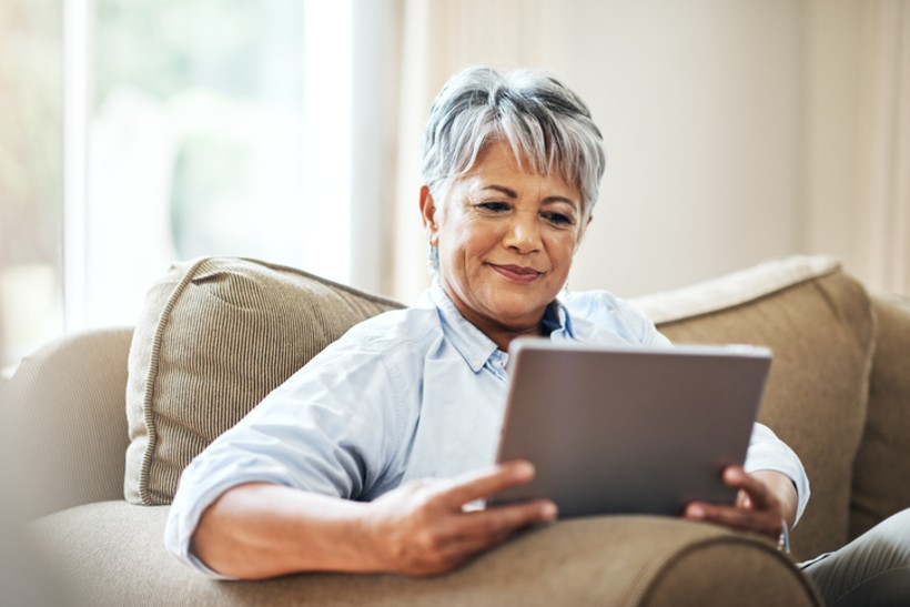 senior woman looking on a tablet while sitting down on a couch