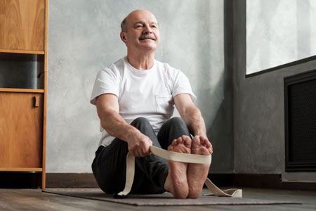 senior man stretches on a yoga mat
