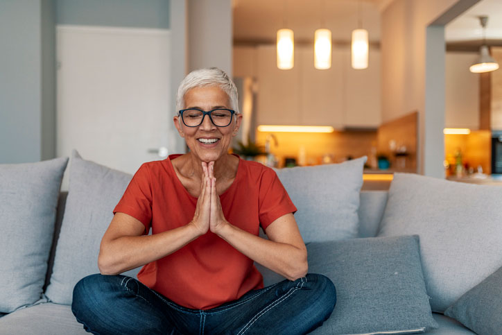 senior woman practices yoga on her couch