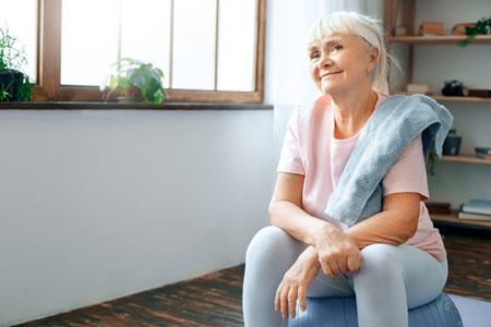 senior woman sits on an exercise ball