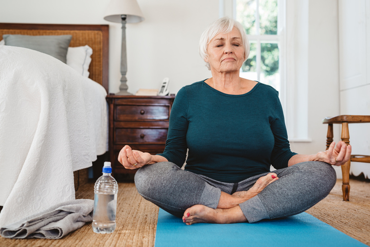 a senior woman practicing yoga alone in her senior apartment
