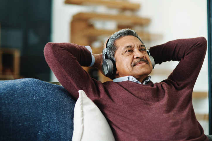 a senior man relaxing and listening to music on a pair of headphones
