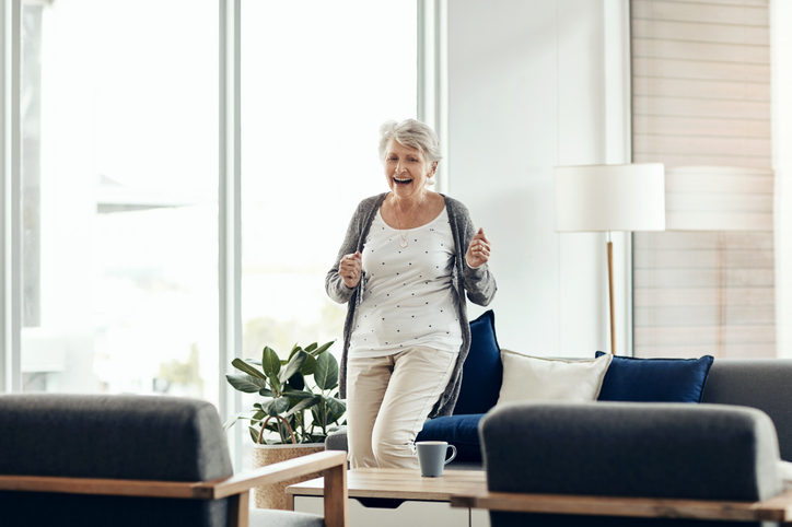 a senior woman dancing and smiling in her independent living apartment