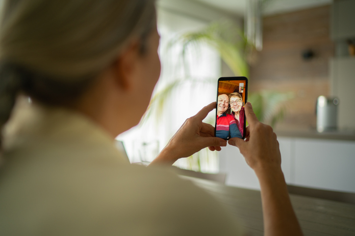 an elderly couple and their adult daughter speaking on a phone using video chat
