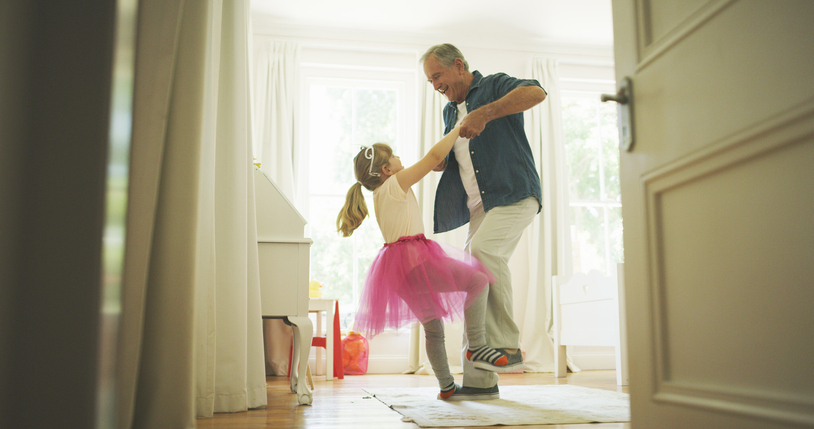a senior man dancing with his granddaughter