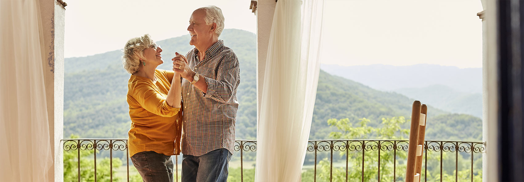 A senior couple dancing on a balcony