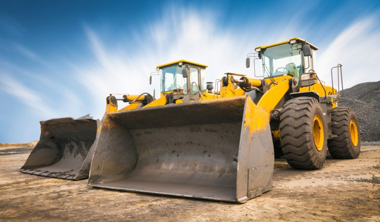 Two yellow heavy-duty buldozers standing on a building site