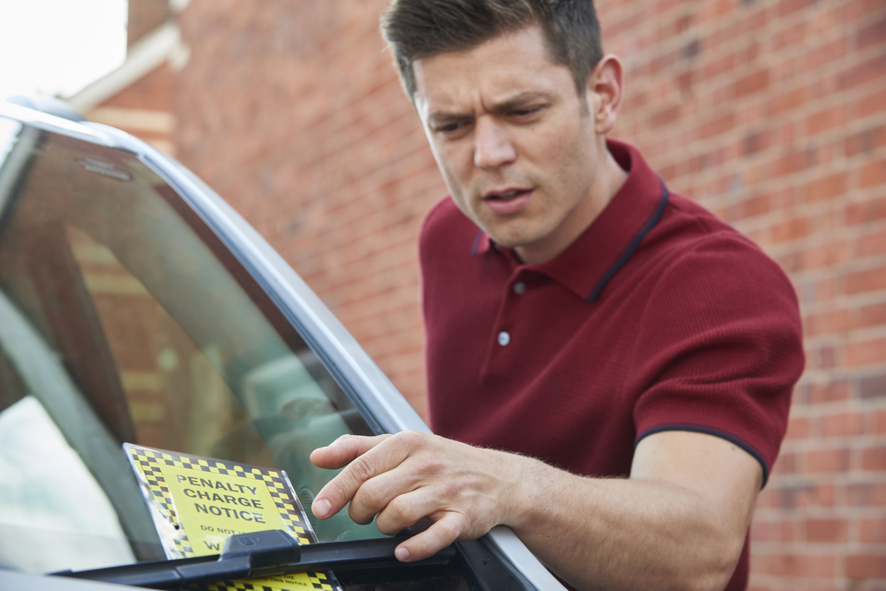 Afraid man looking at penalty charge notice left on his vehicle