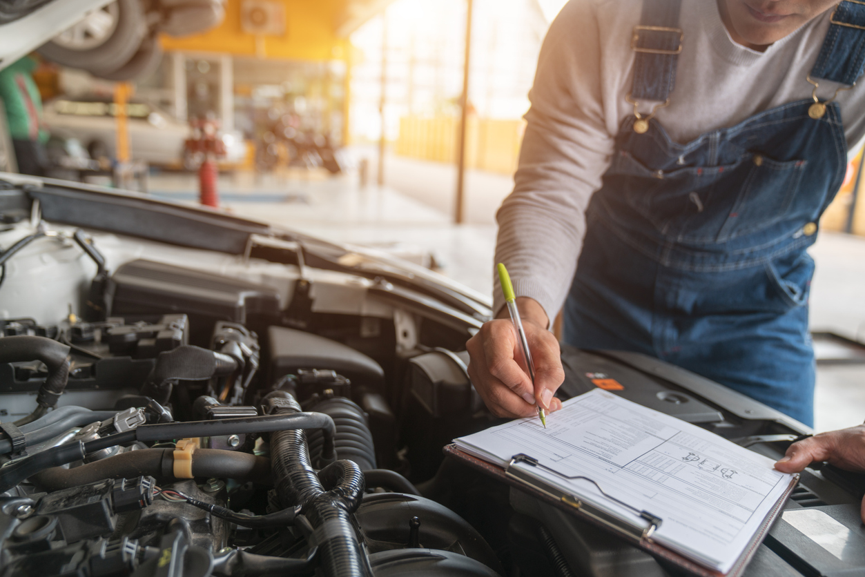 Man with a notepad while performing vehicle inspection