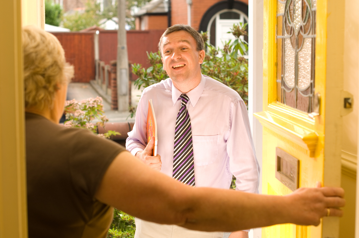 Door-to-door salesman talking to a potential customer