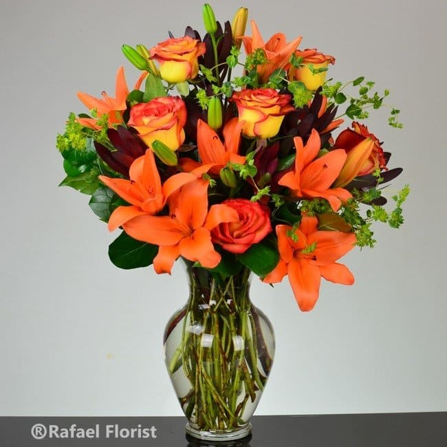 Stunning flower arrangement of orange Fiery Asiatic lilies and roses
