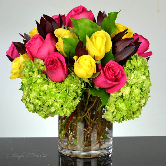 3de60380f0ae Rainbow rose arrangement in a cylinder vase with green hydrangeas