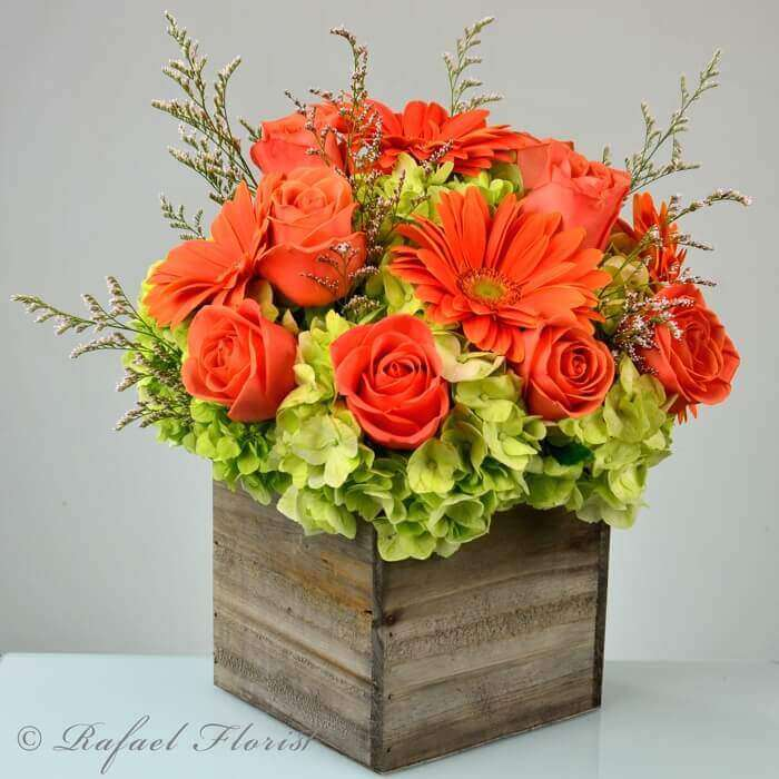 shabby chic flower design of orange roses and gerbera daisies in a ...