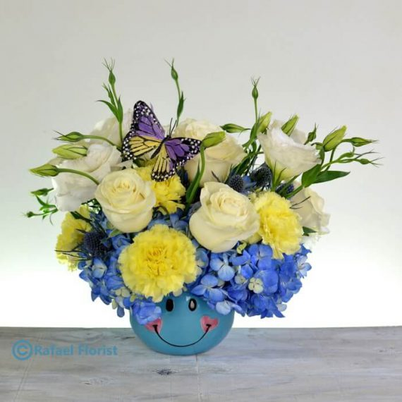 New baby arrangement in blue smiley ceramic with roses & hydrangeas