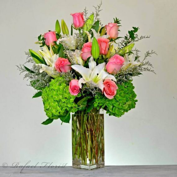 A stunning design of soft pink roses, fragrant white lilies, and ...