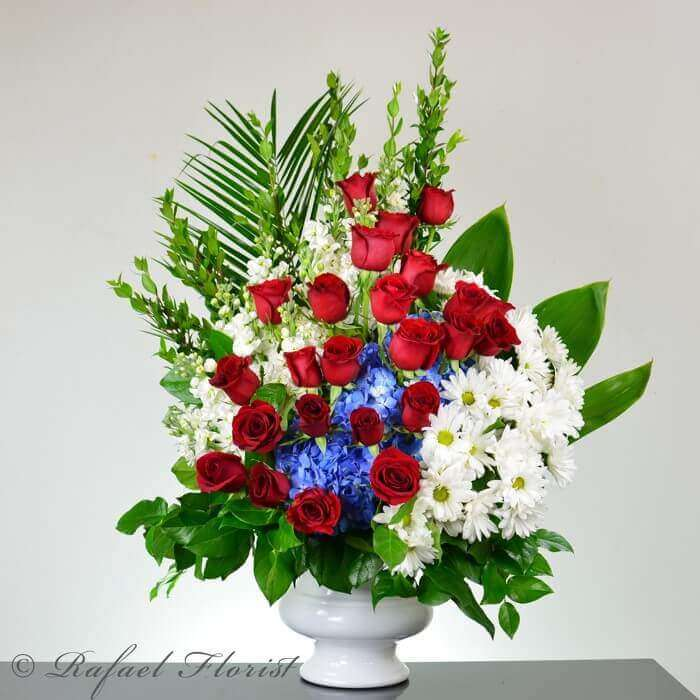 patriotic red white and blue memorial flowers in a white urn