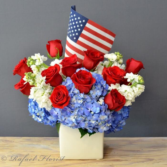 Patriotic arrangement of red roses, white stocks, and blue hydrangeas
