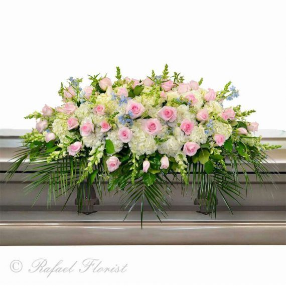 A pastel color casket spray of delicate blooms in pale pinks and whites memorial casket flowers pink roses baby blue belladonna white hydrangeas funeral mightylinksfo