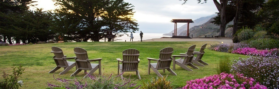 adirondack chairs on grassy area overlooking ocean
