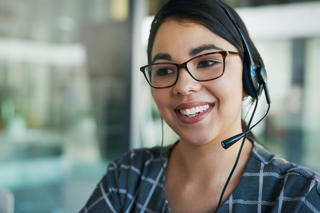 Smiling woman with headset working as part of telephone answering service