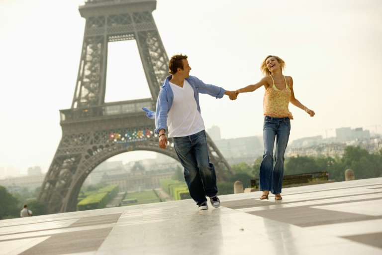 Ungt par framför Eiffeltornet i Paris