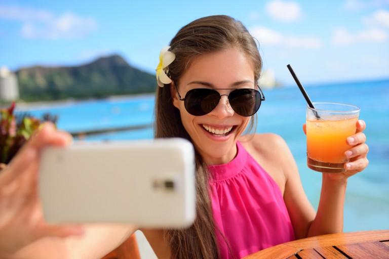 Slappe av med en selfie og juice på stranden