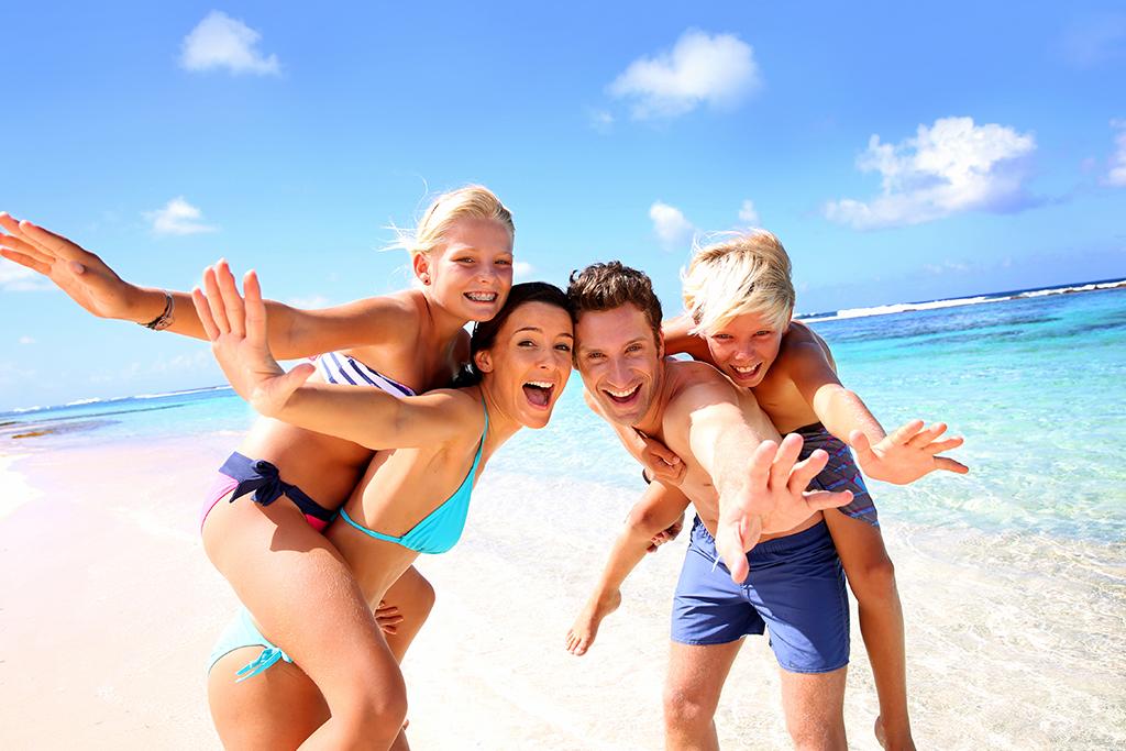 Familien leker og tuller på stranden