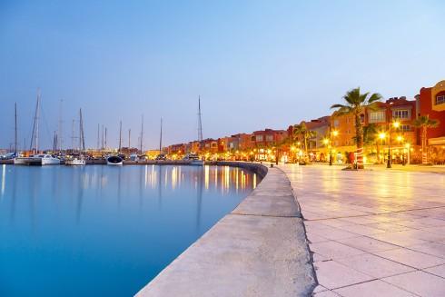 Hurghada marina i kveldssol, opplyst langs promenaden og helt lyseblått hav.