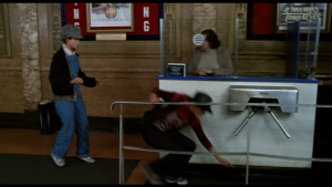 """Nicky and Pammy duck under the theater turnstile and run past a poster for """"A Woman's Torment"""" (1977)"""