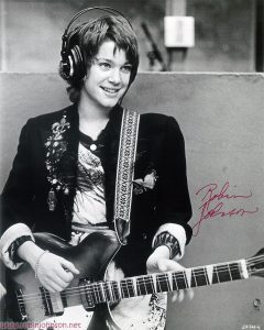 Robin Johnson as Nicky Marotta holding her Rickenbacker in the WJAD radio studio. Image is identified as 69-34A-4 in the lower right-hand corner. Photo is autographed by Robin Johnson (probably around January 1981).