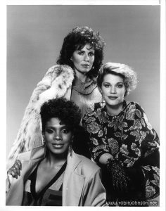 "The three main actresses of Code Name: Foxfire in character. Text [on back]: NBC Photo Press Department 30 Rockefeller Plaza New York, N.Y. 10020 EXCLUSIVE TO YOU IN YOUR CITY LADY SPIES — Joanna Cassidy (center) heads a team of female operatives (Sherly Lee Ralph, left, and Robin Johnson) who work for a special government agency on top-secret missions in NBC-TV's ""Code Name: Foxfire,"" a new, light-hearted, action-adventure series (Fridays, 8-9 p.m. NYT), premiering February 8. (NEW SERIES) (A)(SFP #1 & 2) (1/18/85) © 1985. National Broadcasting Co., Inc. For Editorial Use Relative to NBC-TV Network Broadcast Only. All Other Rights Reserved. [Stamped in blue] RSK 13577 [Handwritten in blue] X-Ref's please """