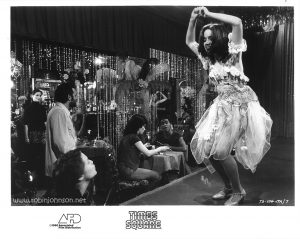 "Publicity still of Robin Johnson, Trini Alvarado, and Miguel Pinero in the Cleo Club, from the ""Times Square"" US Press Materials folder.  Text:  (on image) TS-104-17A/7  (on border) TIMES SQUARE AFD ©1980 Associated Film Distribution"
