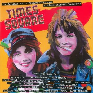 "12"" x 12"" reproduction of the ""Times Square"" soundtrack album cover, used as promotional decoration in record stores. 1980. Text: The Original Motion Picture Soundtrack A Robert Stigwood Production TIMES SQUARE TM Featuring Music Of: SUZI QUATRO, THE PRETENDERS, ROXY MUSIC, GARY NUMAN, ,ARCY LEVY & ROBIN GIBB, TALKING HEADS, JOE JACKSON, XTC, THE RAMONES, ROBIN JOHNSON & TRINI ALVARADO, THE RUTS, D.L. BYRON, LOU REED, DESMOND CHILD & ROUGE, GARLAND JEFFREYS, THE CURE, PATTI SMITH GROUP, DAVID JOHANSEN."