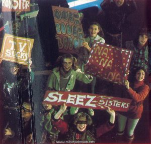 The fourth image from the inner gatefold of the UK edition of the TIMES SQUARE soundtrack album is a photograph of Sleez Girls at the final concert, one of whom is holding a sign referencing a song that does not appear in the film.  Other editions of the soundtrack album have a photo pf Tim Curry in this spot.  (This digital surrogate created by Sean Rockoff for robinjohnson.net)