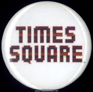 "The ""Times Square"" logo on a white background. Diameter 1 1/2 "". Made by ""F.A.M.E. Hollywood."""