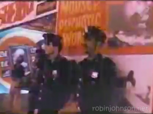"The pair of cops beneath the ""House of Psychotic Women"" poster, a shot from the TIMES SQUARE soundtrack promotional video that does not appear in the movie."